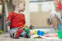Adorable cute caucasian little blond siblings children enjoy having fun painting with brush and palm at home indoors