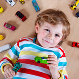 Adorable cute child with lot of different colorful toy cars Stock Images