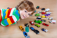 Adorable cute child with lot of different colorful toy cars Royalty Free Stock Photos