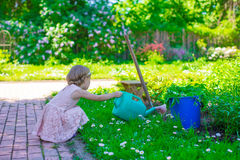 Adorable cute girl with a watering can at big Royalty Free Stock Photography