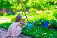 Adorable cute girl with a watering can at big Stock Photos