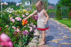 Adorable cute girl watering flowers with a Stock Images