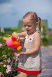 Adorable cute girl watering flowers with a Royalty Free Stock Photo