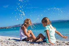Adorable cute girls have fun on white beach during Royalty Free Stock Photos