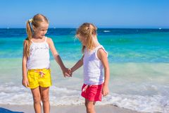 Adorable cute girls have fun on white beach during Stock Photography
