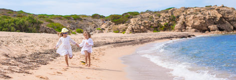 Adorable cute girls have fun on white beach during Royalty Free Stock Image
