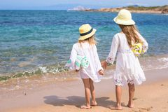 Adorable cute girls walking on white beach during Stock Image