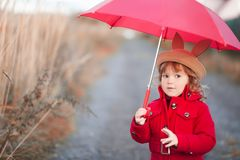 Little girl walking with umbrella, autumn day. Stock Photos