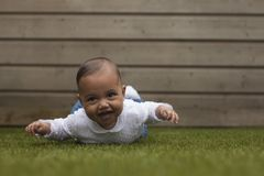 Adorable cute little baby girl lying on belly on grass surface w stock image
