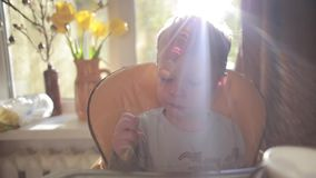 Adorable, cute little boy sitting in high chair, eating, laughing and smiling in sun rays in front of big window stock video footage