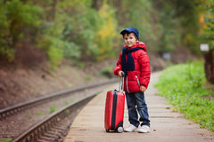 Adorable cute little child, boy, waiting on a railway station fo Stock Photo