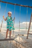 Adorable cute little girl in a dress and. Sunglasses on swing on white sandy Caribbean beach. This image has attached release Stock Photo