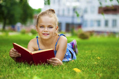Adorable cute little girl reading book outside on grass Royalty Free Stock Image