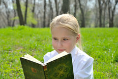 Adorable cute little girl reading book outside on. Adorable cute little girl reading book sitting outside on grass Royalty Free Stock Image