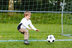 Adorable cute little kid boy playing soccer and football on field Stock Photo