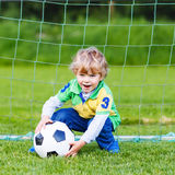 Adorable cute little kid boy playing soccer and football on field stock photos