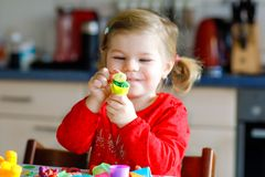 Adorable cute little toddler girl with colorful clay. Healthy baby child playing and creating toys from play dough stock photo