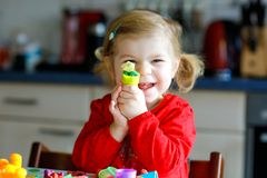 Adorable cute little toddler girl with colorful clay. Healthy baby child playing and creating toys from play dough royalty free stock photo