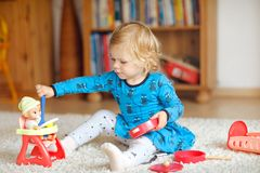 Adorable cute little toddler girl playing with doll. Happy healthy baby child having fun with role game, playing mother Royalty Free Stock Photos