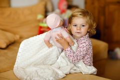 Adorable cute little toddler girl playing with doll. Happy healthy baby child having fun with role game, playing mother Stock Photography