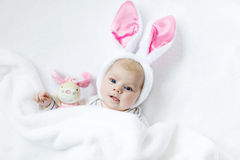 Adorable cute newborn baby girl in Easter bunny costume and ears. Lovely child playing with plush rabbit toy. Holiday concept Stock Photo