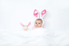 Adorable cute newborn baby girl in Easter bunny costume and ears. Lovely child playing with plush rabbit toy. Holiday concept Royalty Free Stock Image