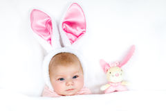 Adorable cute newborn baby girl in Easter bunny costume and ears. Lovely child playing with plush rabbit toy. Holiday concept Stock Images