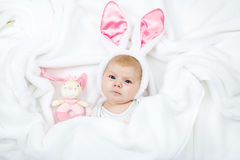Adorable cute newborn baby girl in Easter bunny costume and ears. Lovely child playing with plush rabbit toy. Holiday concept Royalty Free Stock Photos