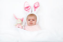 Adorable cute newborn baby girl in Easter bunny costume and ears. Lovely child playing with plush rabbit toy. Holiday concept Stock Image