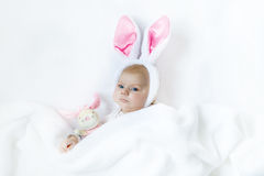 Adorable cute newborn baby girl in Easter bunny costume and ears. Lovely child playing with plush rabbit toy. Holiday concept Stock Photos