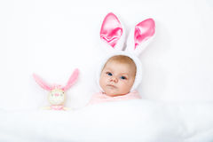 Adorable cute newborn baby girl in Easter bunny costume and ears. Lovely child playing with plush rabbit toy. Holiday concept Royalty Free Stock Images
