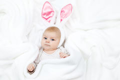 Adorable cute newborn baby girl in Easter bunny costume and ears. Lovely child playing with plush rabbit toy. Holiday concept Royalty Free Stock Photography