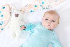 Adorable cute newborn baby girl with Easter bunny toy. Close-up of adorable cute newborn baby girl of two months on white background. Lovely child playing with Royalty Free Stock Photo