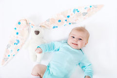 Adorable cute newborn baby girl with Easter bunny toy. Close-up of adorable cute newborn baby girl of two months on white background. Lovely child playing with Stock Images