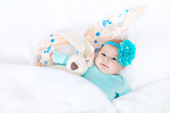 Adorable cute newborn baby girl with Easter bunny toy. Close-up of adorable cute newborn baby girl of two months on white background. Lovely child playing with Royalty Free Stock Images