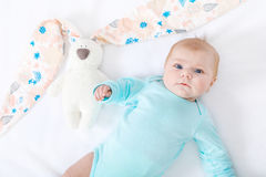 Adorable cute newborn baby girl with Easter bunny toy. Close-up of adorable cute newborn baby girl of two months on white background. Lovely child playing with Stock Photos