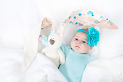 Adorable cute newborn baby girl with turquoise flower headband with Easter bunny Stock Photos