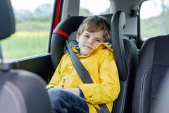 Adorable cute preschool kid boy sitting in car in yellow rain coat. Little school child in safety car seat with belt enjoying trip and jorney. Safe travel with stock image