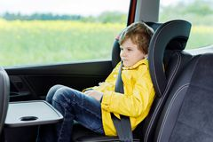 Adorable cute preschool kid boy sitting in car in yellow rain coat. Little school child in safety car seat with belt enjoying trip and jorney. Safe travel with stock photography