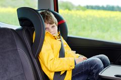Adorable cute preschool kid boy sitting in car in yellow rain coat. Little school child in safety car seat with belt. Enjoying trip and jorney. Safe travel with stock photography
