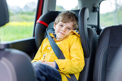 Adorable cute preschool kid boy sitting in car in yellow rain coat. Little school child in safety car seat with belt enjoying trip and jorney. Safe travel with royalty free stock photos
