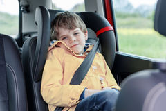 Adorable cute preschool kid boy sitting in car in yellow rain coat. Little school child in safety car seat with belt enjoying trip and jorney. Safe travel with stock images