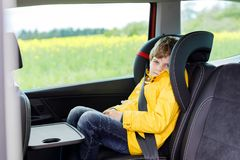 Adorable cute preschool kid boy sitting in car in yellow rain coat. Little school child in safety car seat with belt enjoying trip and jorney. Safe travel with stock photo
