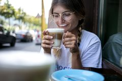 Cute pretty young woman drinks coffee milk foam stock photography