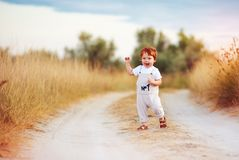 Adorable redhead toddler baby boy in jumpsuit running along rural summer road in sunburned field. Adorable cute redhead toddler baby boy in jumpsuit running royalty free stock photography