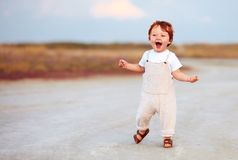 Adorable redhead toddler baby boy in jumpsuit running through the summer road and field. Adorable cute redhead toddler baby boy in jumpsuit running through the royalty free stock images