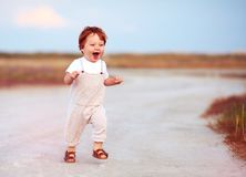 Adorable redhead toddler baby boy in jumpsuit running through the summer road and field. Adorable cute redhead toddler baby boy in jumpsuit running through the Royalty Free Stock Photos