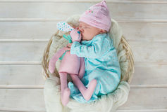 Adorable cute sweet baby girl sleeping in white basket on wooden floor hugging toy tilda rabbits Stock Image