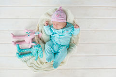 Adorable cute sweet baby girl sleeping in white basket on wooden floor with two toy tilda rabbits Stock Photo