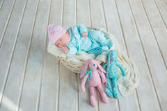 Adorable cute sweet baby girl sleeping in white basket on wooden floor with two toy tilda rabbits Stock Image